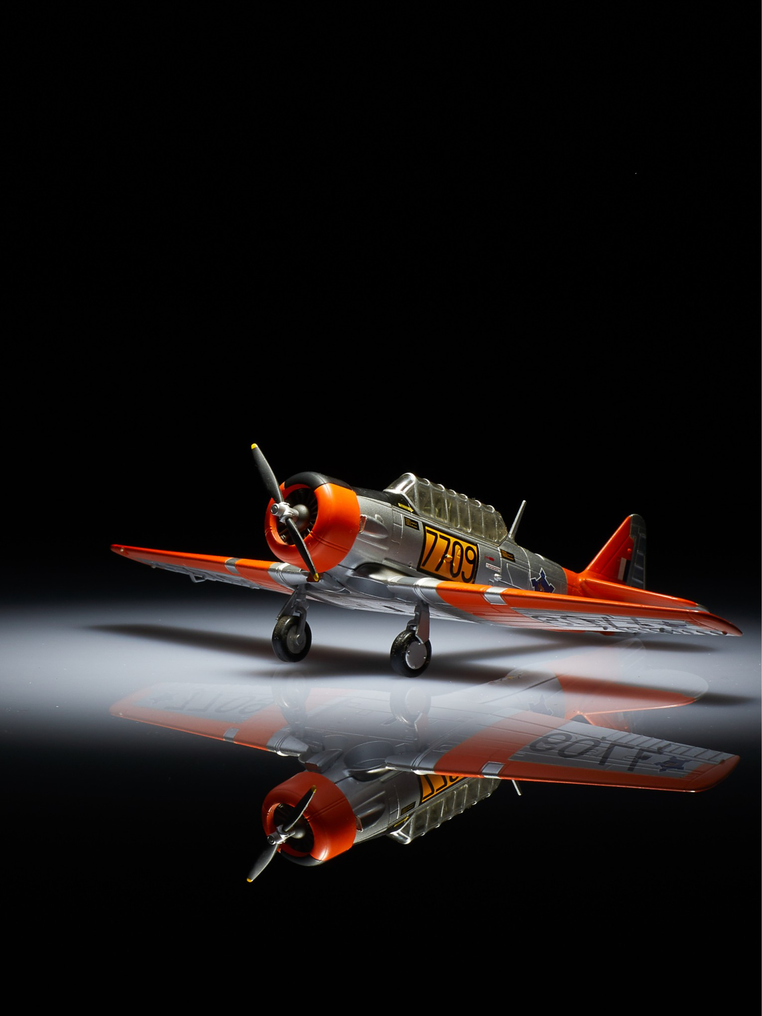Harvard trainer model aircraft on reflective surface